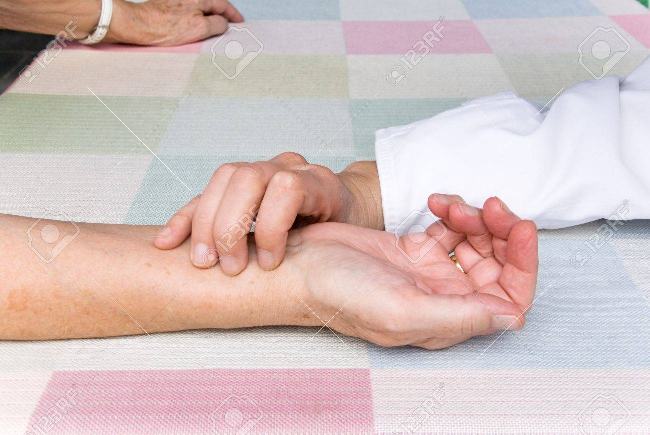 hand of a physician, measuring the pulse rate of a senior patient Stock Photo - 7916437