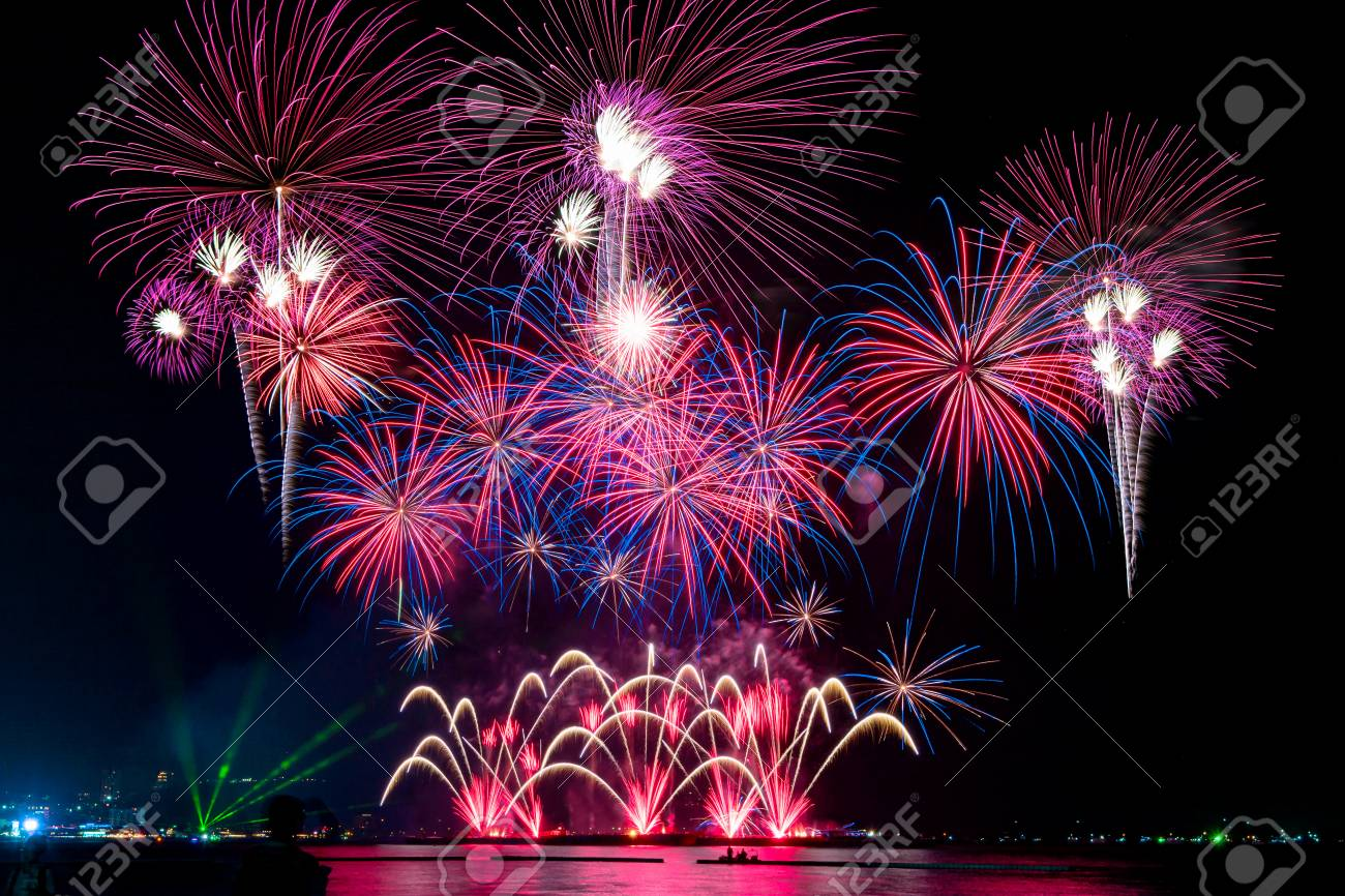 Amazing colorful fireworks display for celebration night on the sea with blur city night background. Celebrate on Christmas and countdown to happy new year concept. - 122891550