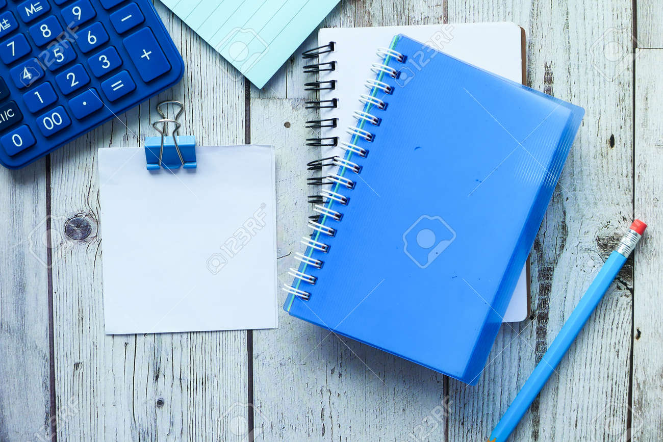 high angle view of notepad and stationary on wooden table - 153332656