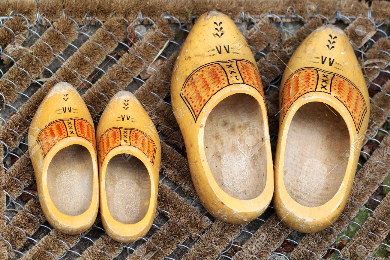 pair of traditional dutch yellow wooden shoes outside a home