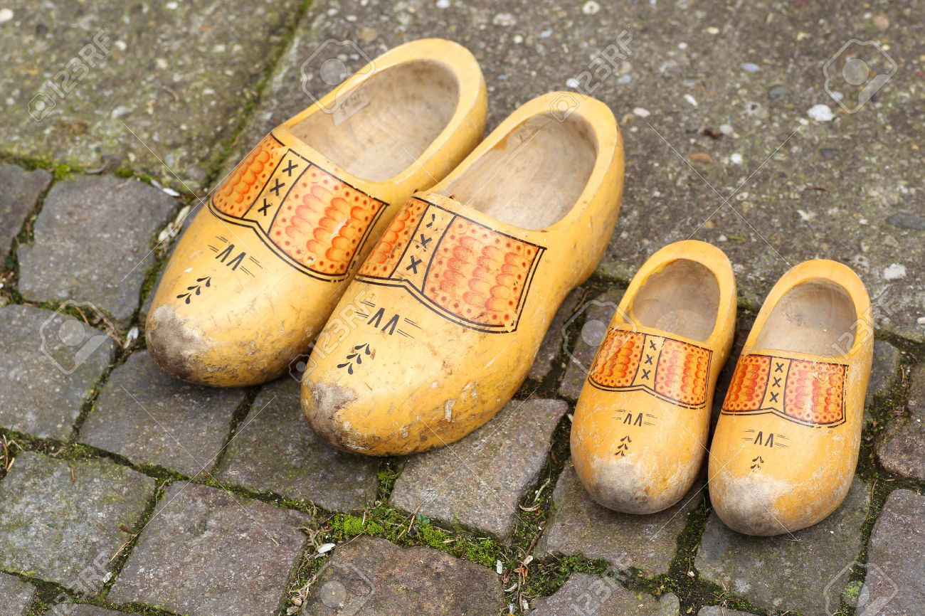 pair of traditional dutch yellow wooden shoes on a stone footpath