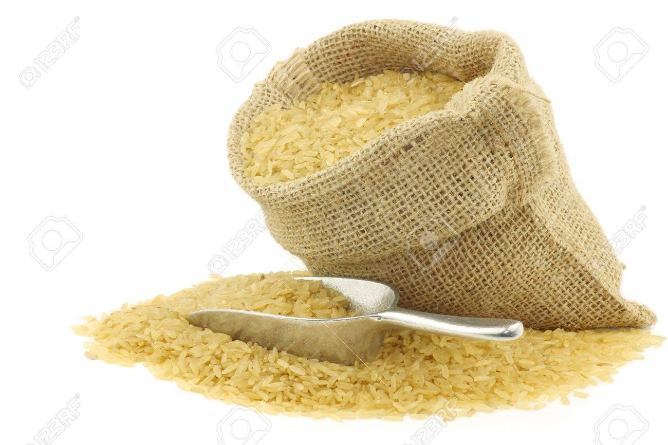 grano de arroz sin pulir todo en una bolsa de arpillera con una cuchara de aluminio