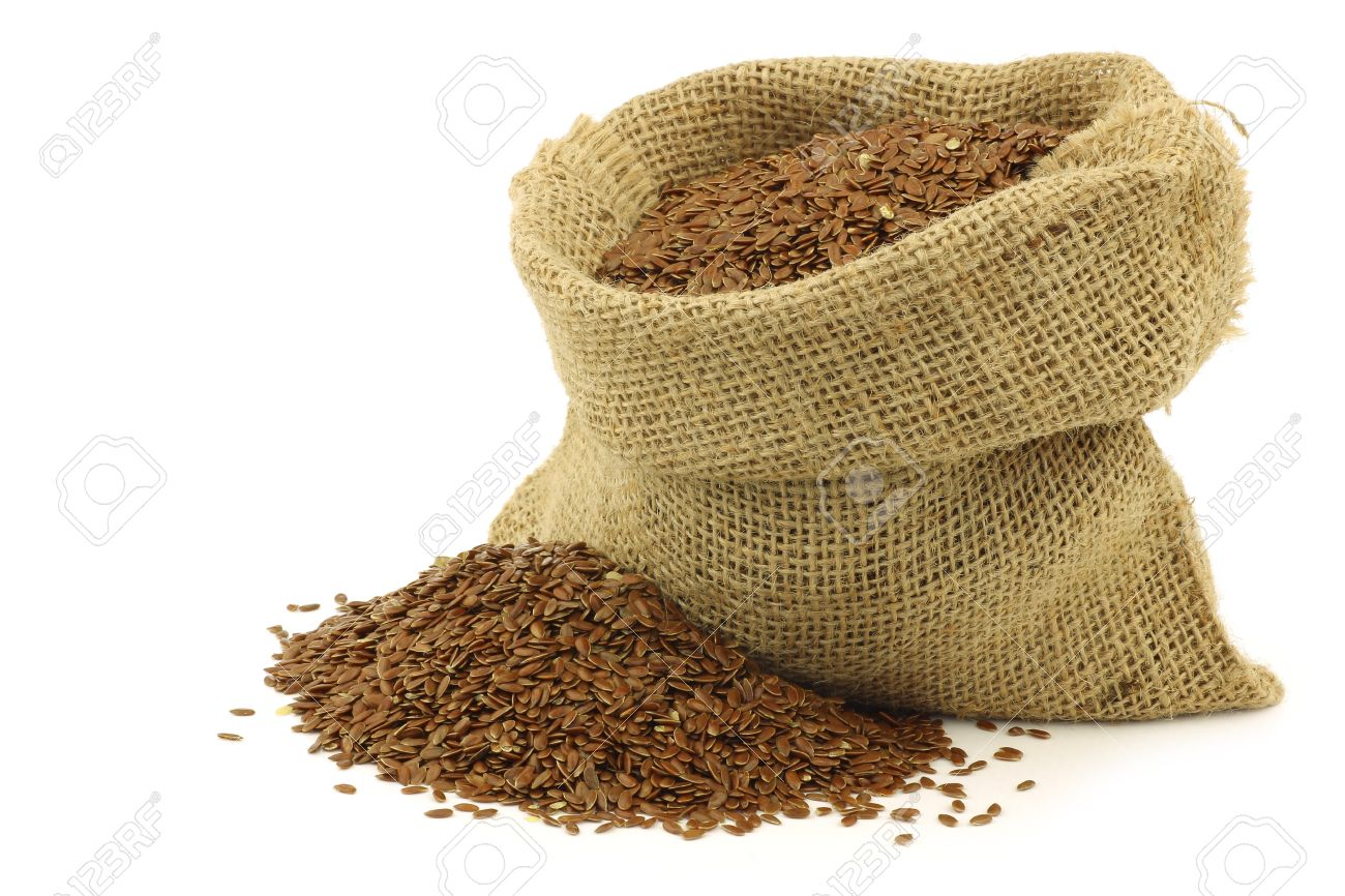 la semilla de lino linaza en una bolsa de arpillera en un fondo blanco foto de