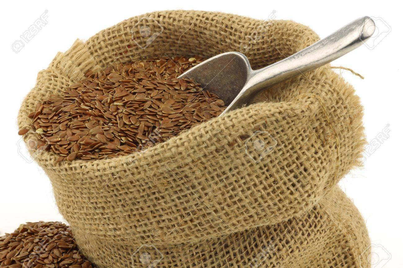 foto de archivo la semilla de lino linaza en una bolsa de arpillera con una cuchara de aluminio sobre un fondo blanco