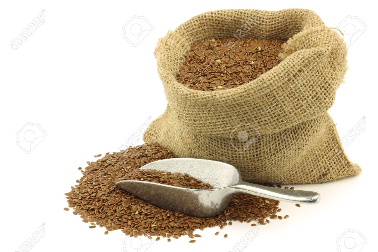 Flax seed  linseed  in a burlap bag with an aluminum scoop on a white background Stock Photo - 15107540