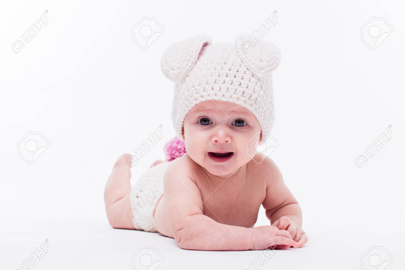 8fdedba0ecb3 Cute baby girl lying on a white background wearing a hat in the form of a