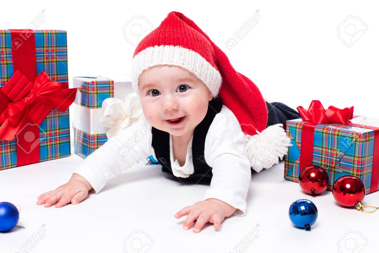 c9c640b37a1b Cute baby in a red New Years cap with a smile on his face lying on his  stomach on a white background surrounded by boxes with gifts, and blue and  red ...