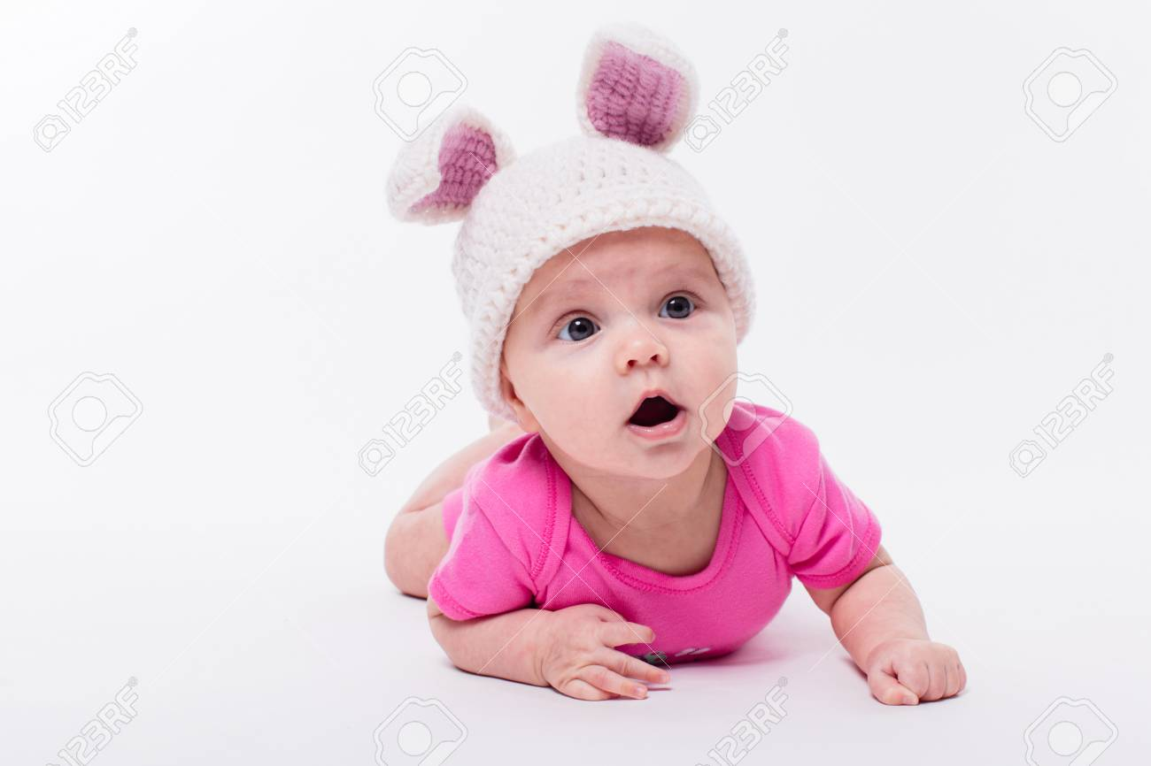 5796f3132f05 cute baby girl lying in a bright red T-shirt on a white background wearing  a hat in the form of a Christmas bunny with pink ears and tail, with depth  of ...