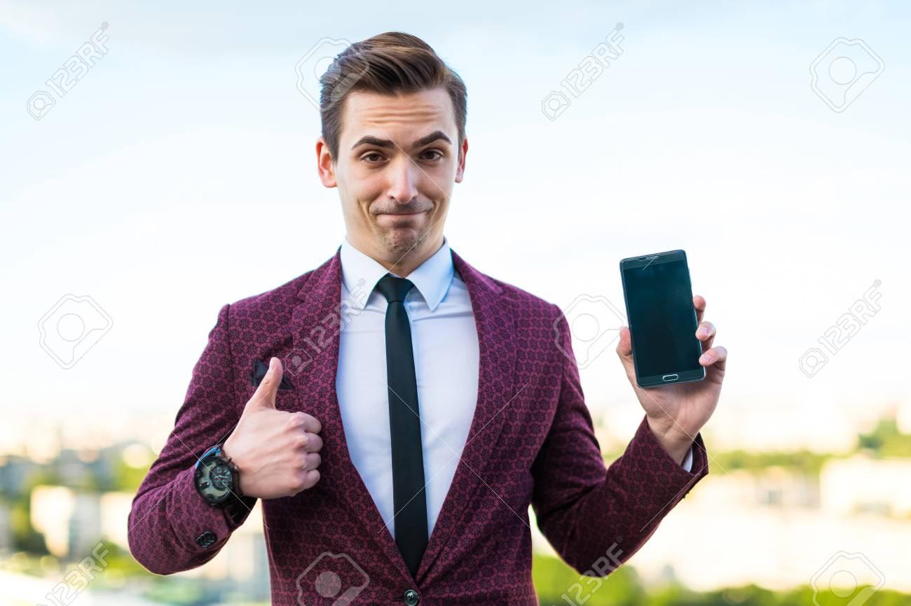 Kaukasischer Geschaftsmann Des Attraktiven Jungen Brunette Im Roten Anzug Im Weissen Hemd In Der Abendgarderobe In Der Schwarzen Hose Und In Der Teuren Uhr Stehen Auf Dem Dach Und Halten Schwarzes Mobiltelefon