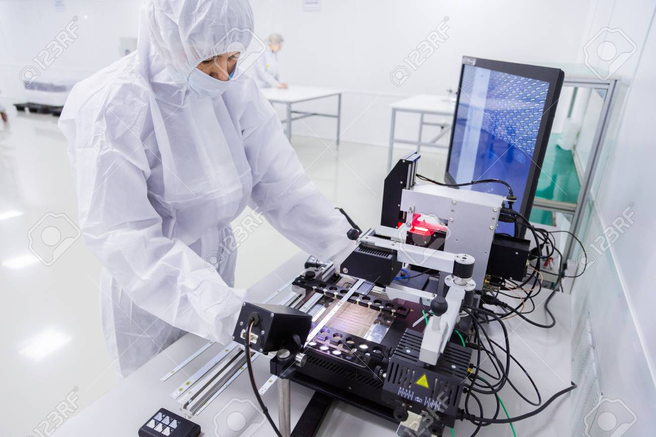 a factory worker in a white lab suit, latex gloves and face mask, working with some modern equipment during the manufacturing of a tv set. - 91281323