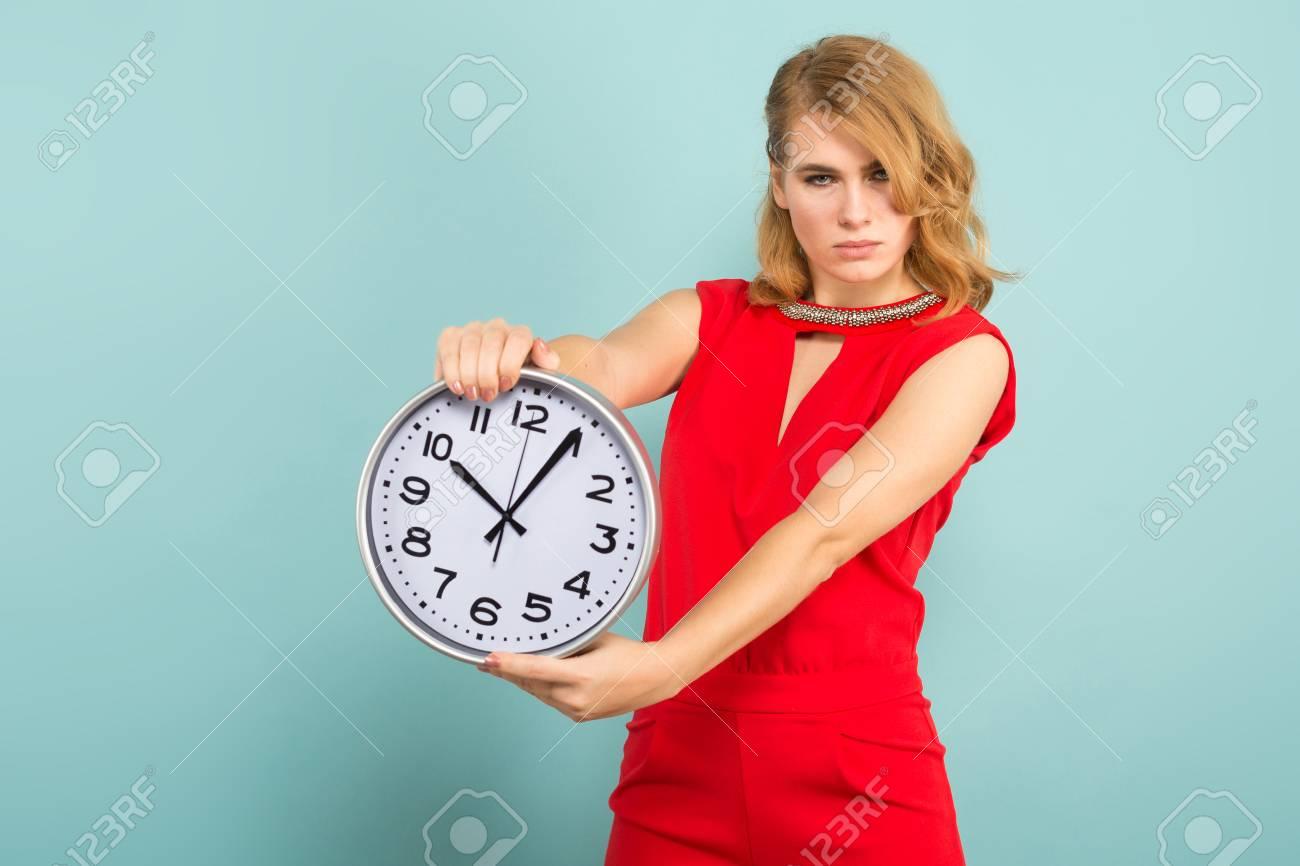 55f4cc39700a85 Archivio Fotografico - Ritratto della donna bionda attraente nel rosso  isolato sul concetto blu di puntualità di tempo degli orologi della tenuta  del fondo.