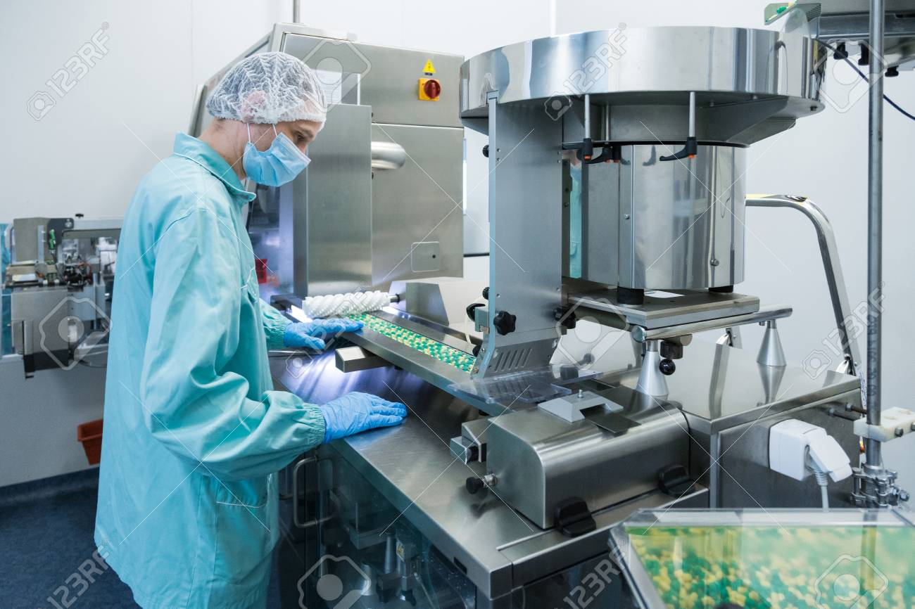 Pharmaceutical technician in sterile environment working on production of pills at pharmacy factory - 103389524