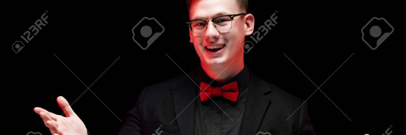 c63f6cd41466 Stock Photo - Young caucasian elegant serious smart successful business man  in black suit with bow-tie standing in office looking in camera smiling  happy