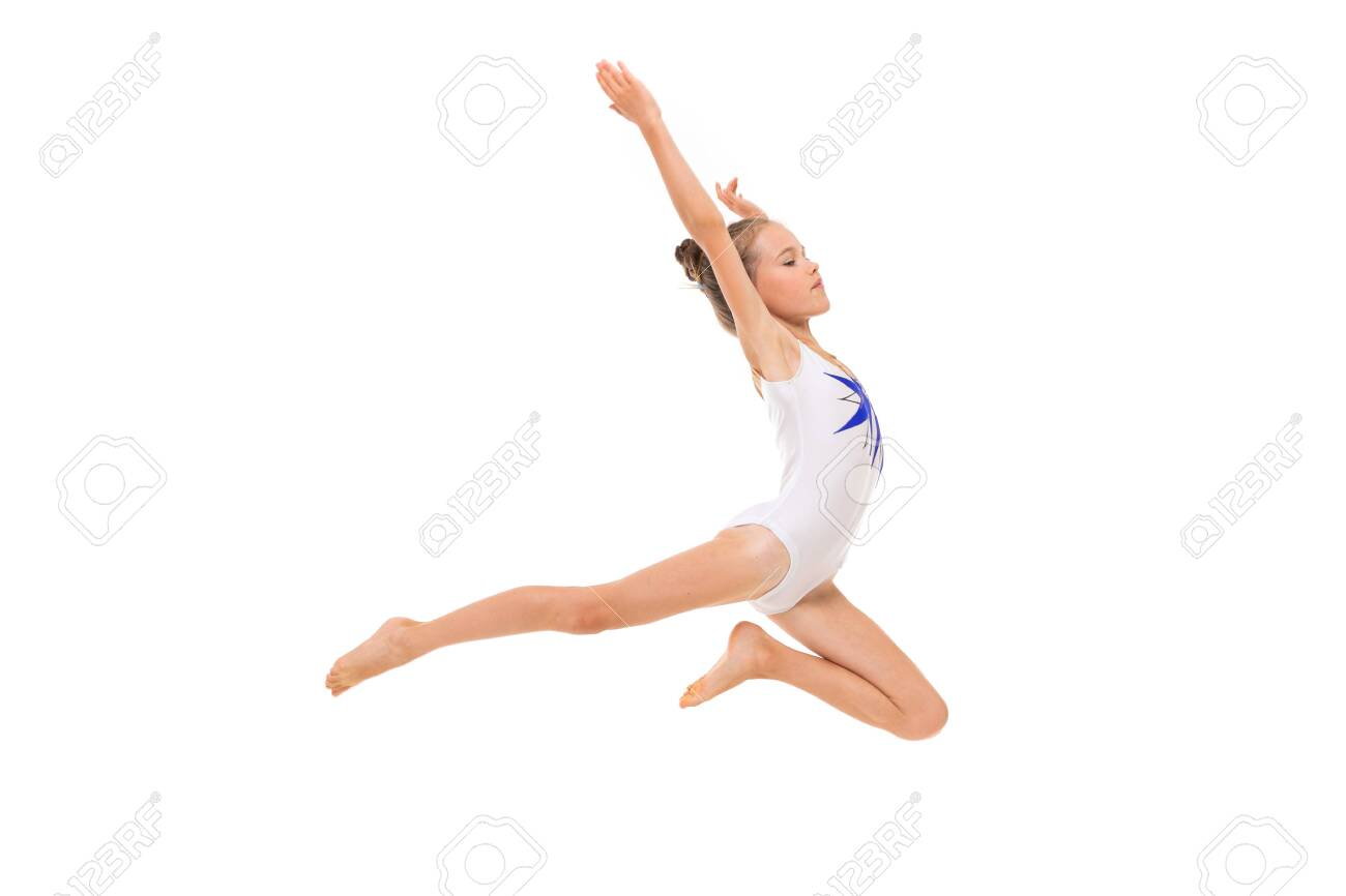 girl gymnast in white trico in full height performs in a white jump - 132840488