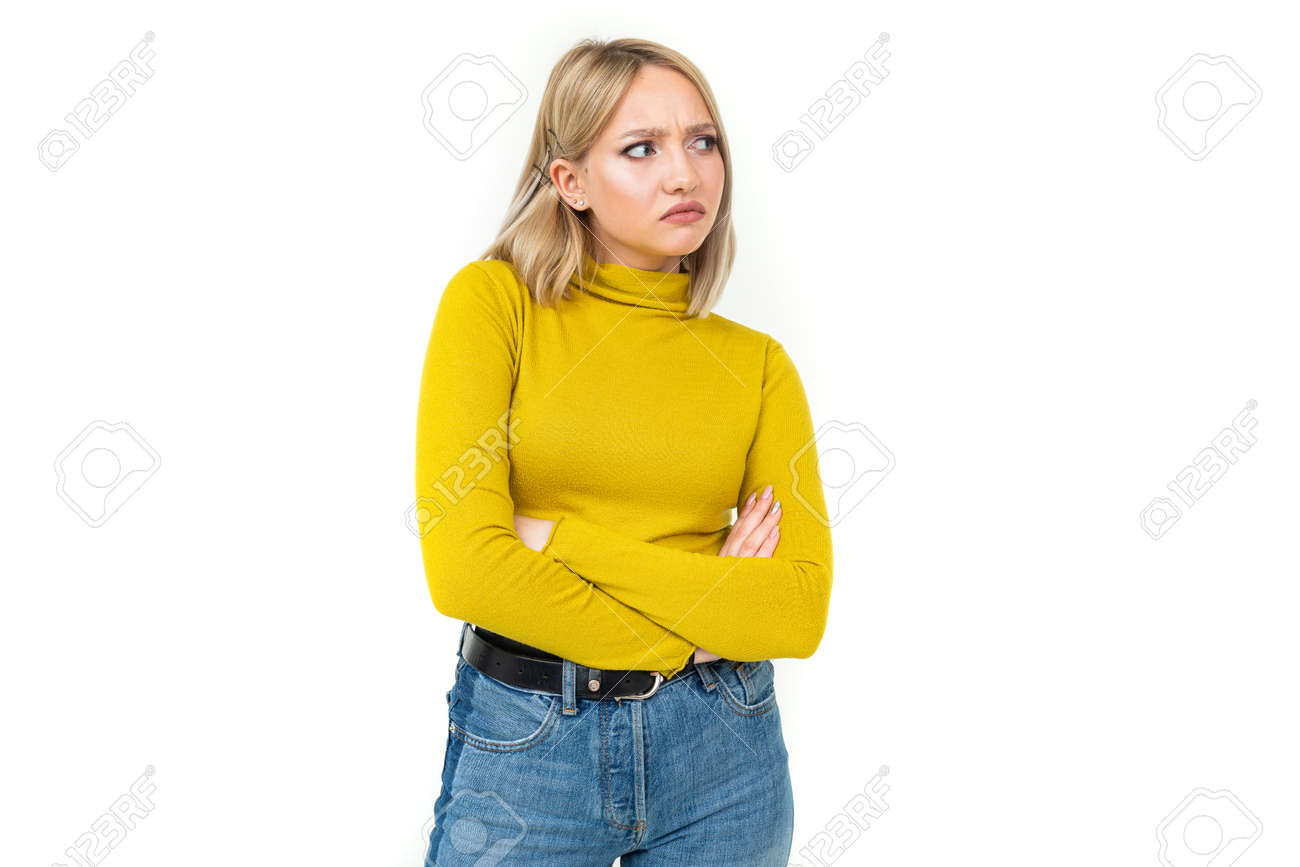 close-up of a young woman with blonde hairstyle dressed in jeans and a yellow sweater with an indignant look on her face on a white isolated background. - 146207532