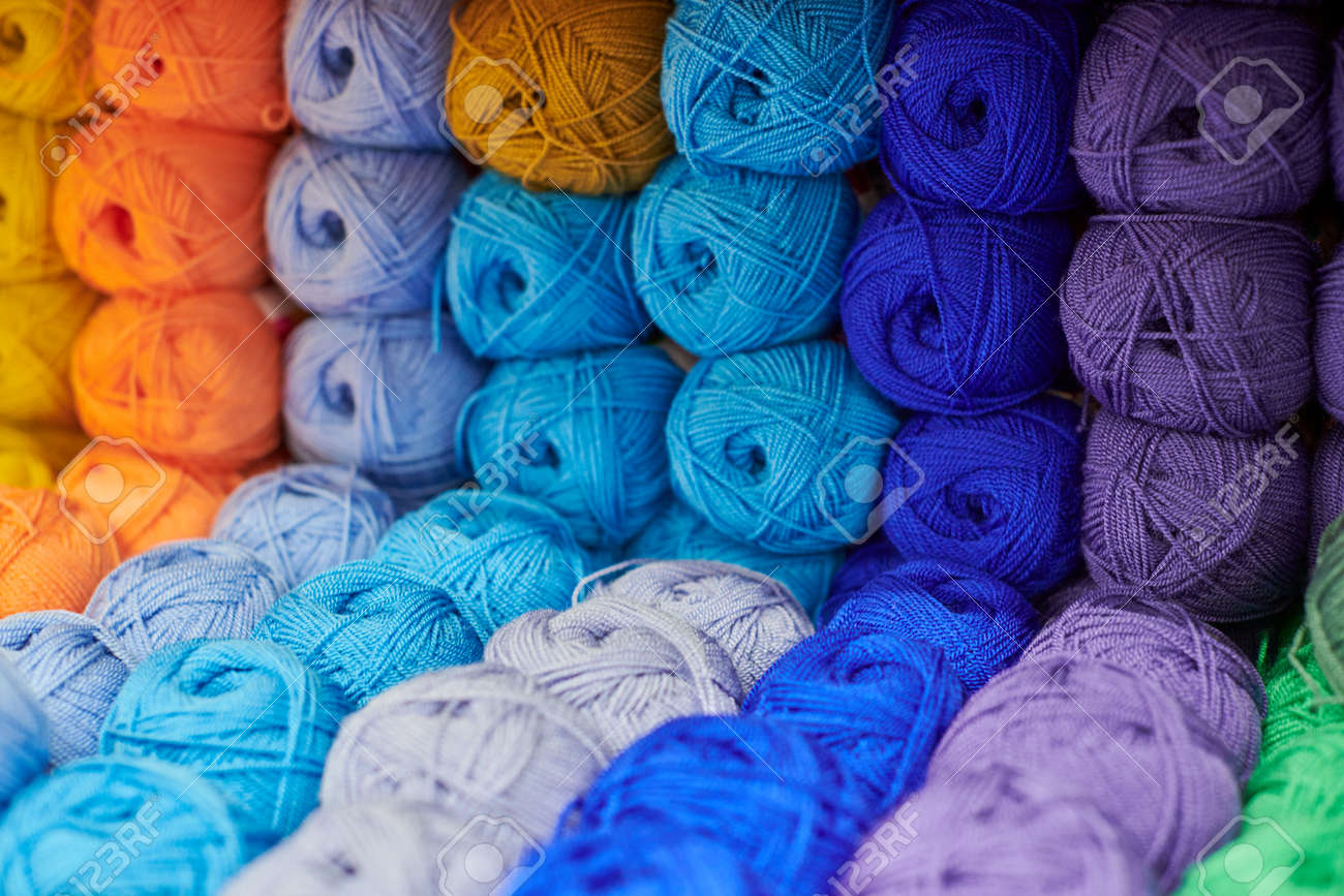Yarns or balls of wool on shelves in store for knitting and needlework, close up. Accessories for haberdashery in fabric store shelves. Multicolored picture, background. - 167351688