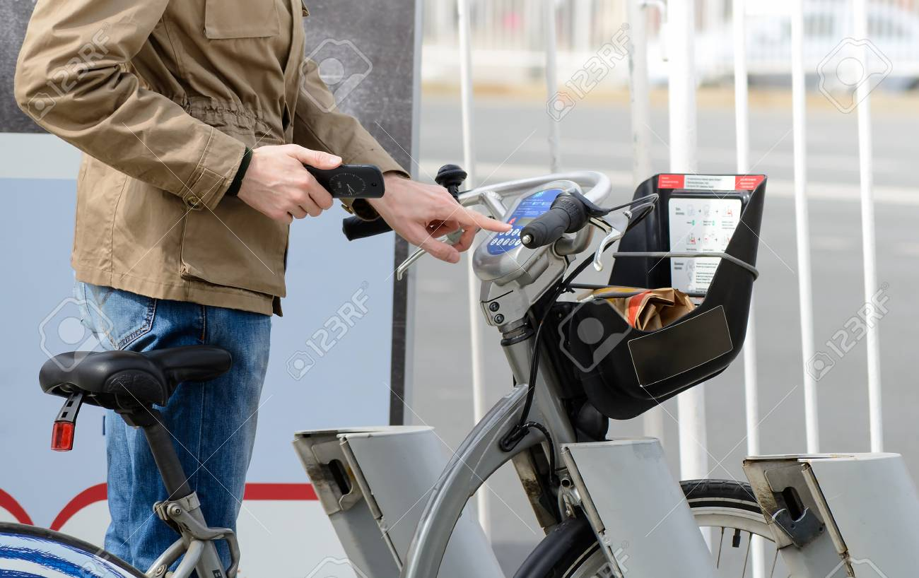 Man taking a bicycle in a bike sharing city service - 77651871