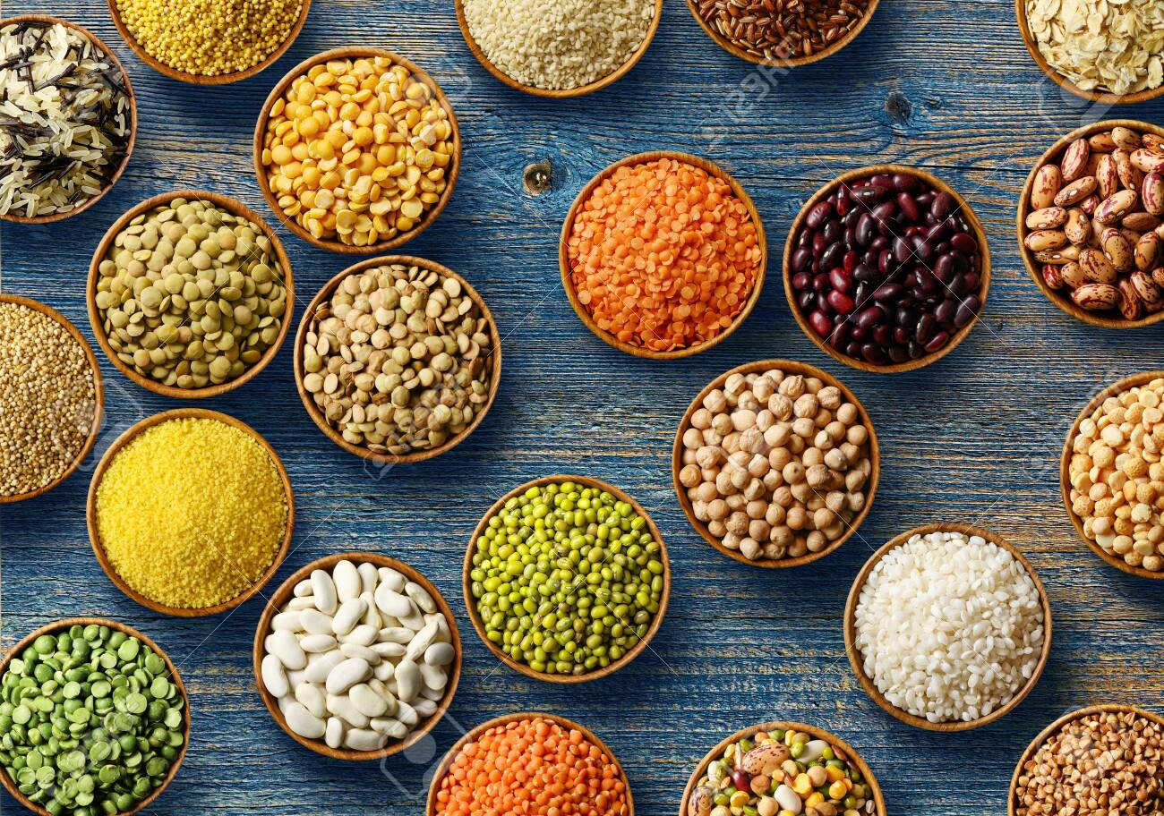 Cereals and legumes in wooden bowls on old wooden background. Food theme background. Flat lay - 140894769