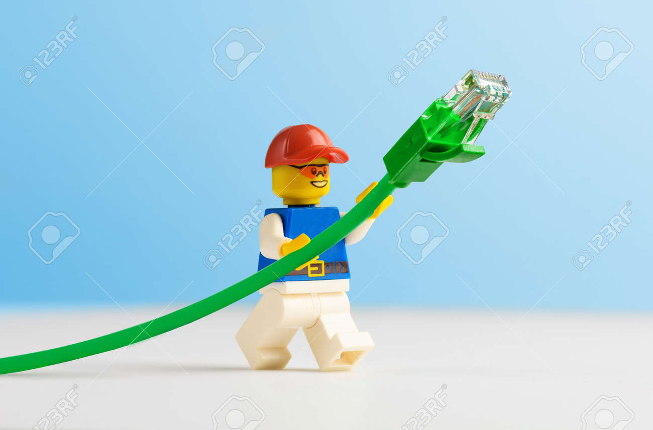Minifigure Technician holding green network cable. - 170784336