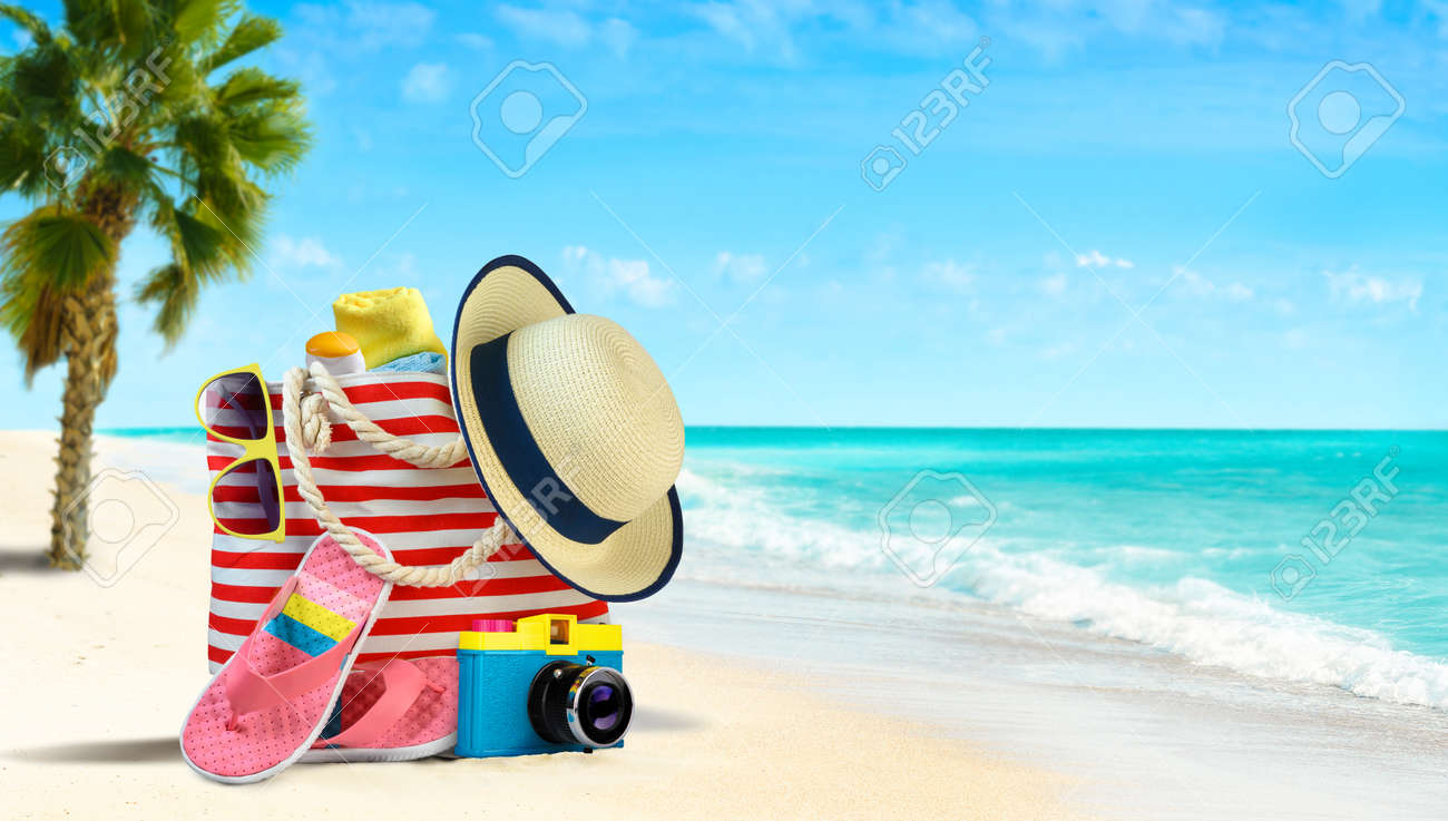 Summer beach bag and accessories - straw hat, flip flops and sunglasses on sandy beach and azure sea on background - 169711072