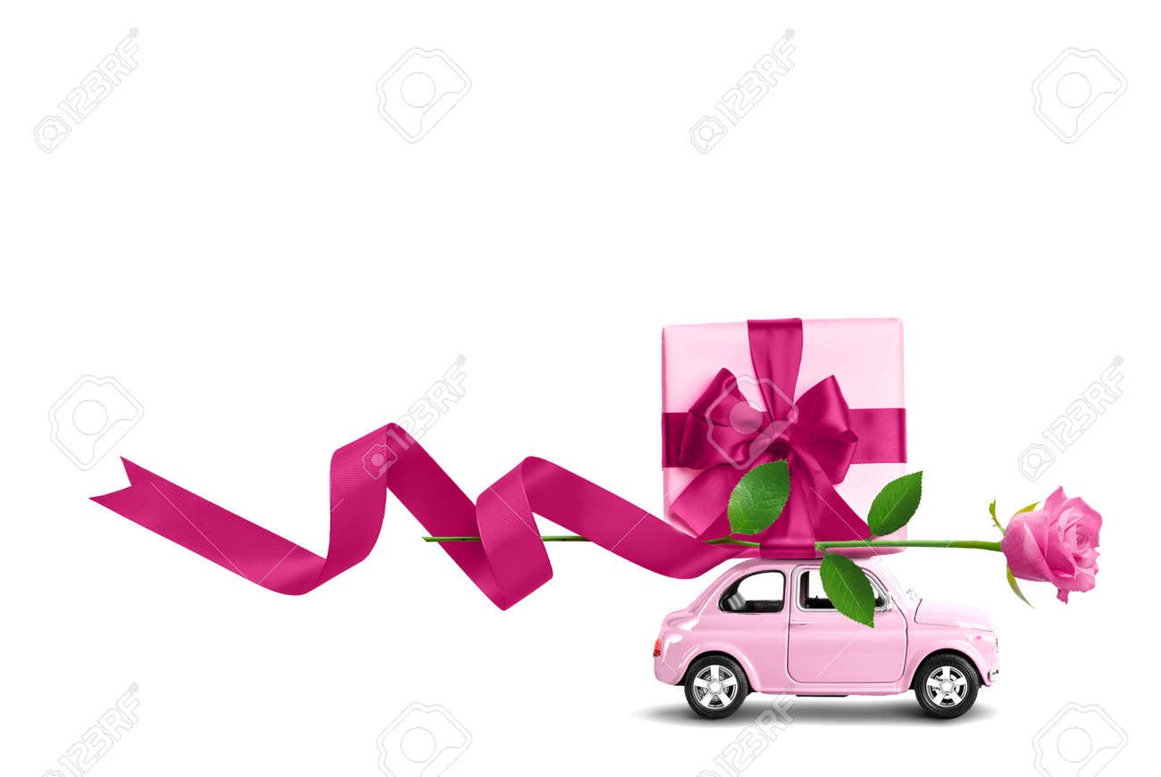 Pink toy car with gift box on a roof and rose flower isolated on a white - 169711168