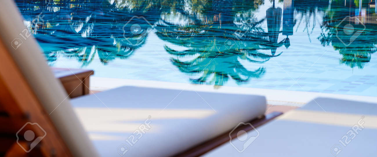 Blank sunbeds and swimming pool in luxury resort - 169711175