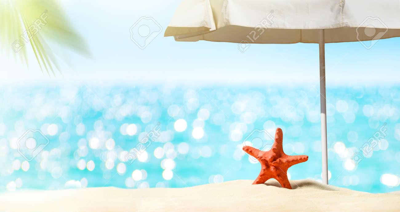 Summer vacation background. Sea, sand beach, umbrella - 169711234