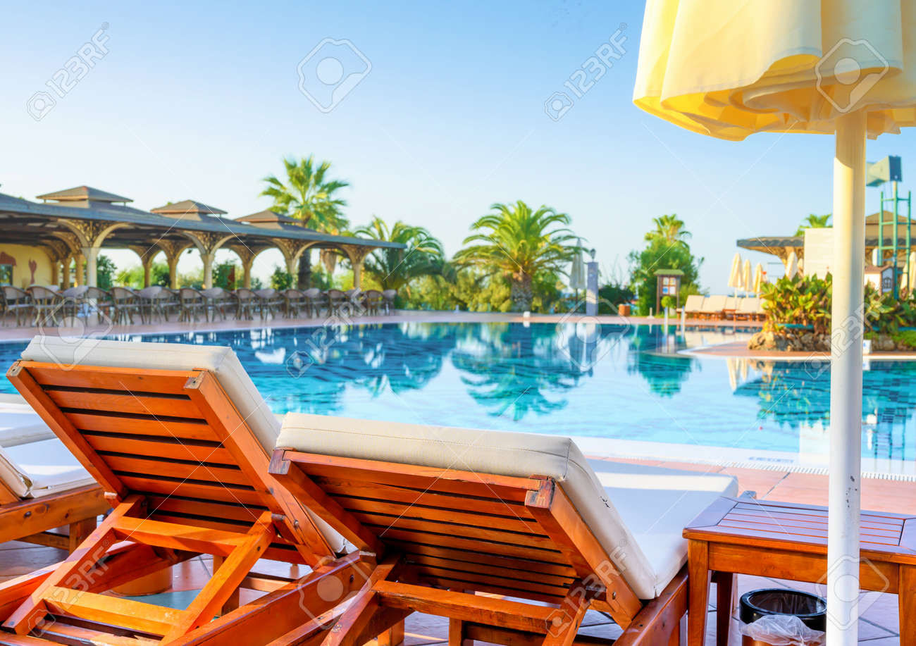 Empty sunbeds and swimming pool in luxury resort - 170946836