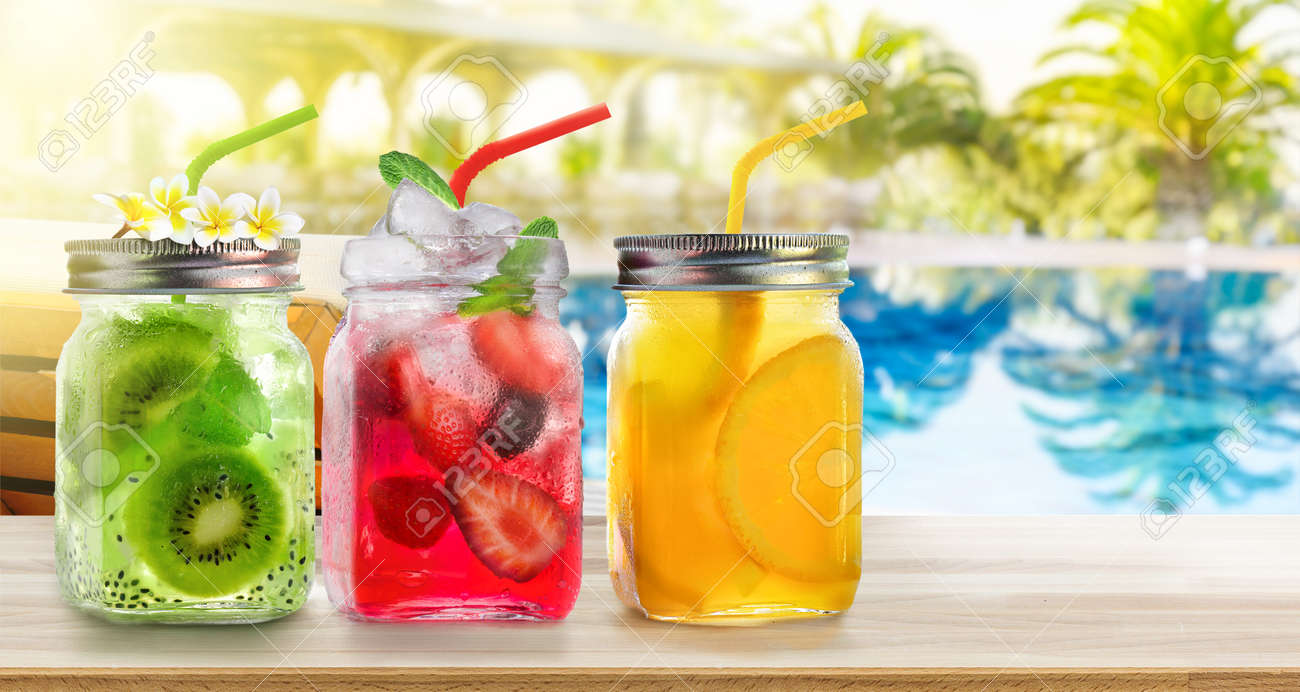 Summer refreshing exotic drinks cocktails in glass jars with straws on wooden counter on swiming pool background. - 170946841