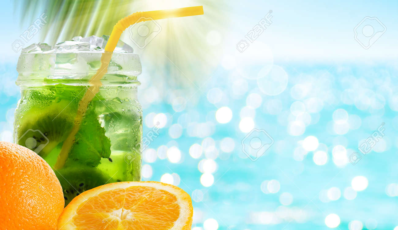 Kiwi cocktail drink with mint leaves in glass jar and orange fruit - 170946840
