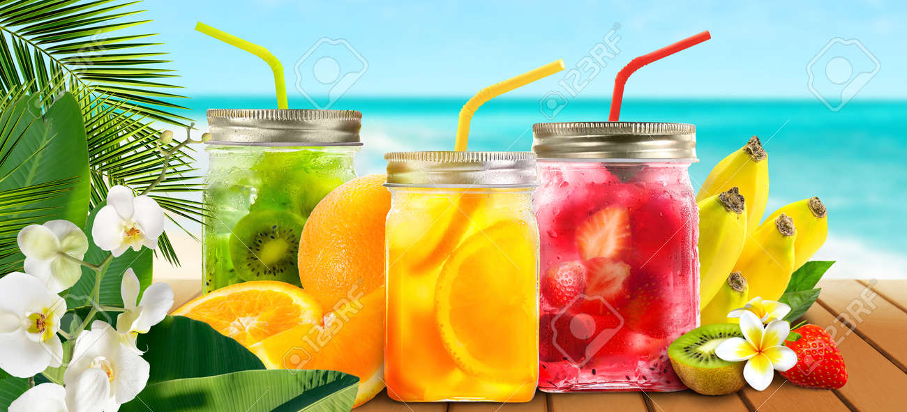 Summer refreshing exotic drinks cocktails in glass jars with tropical fruits on wooden table on seascape background. - 170464772
