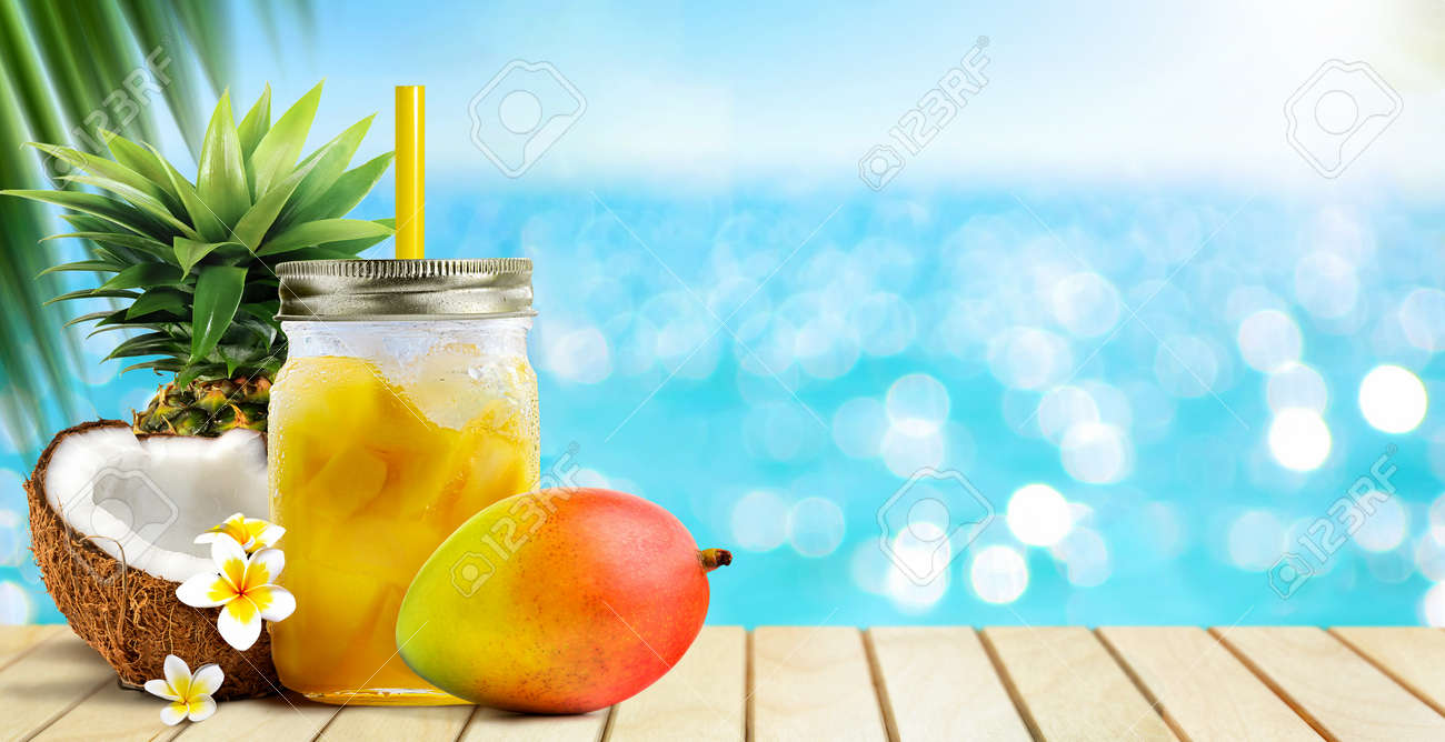 Summer tropical cocktail drink of mango fruit and coconut juice on blue turquoise sea background - 170666594