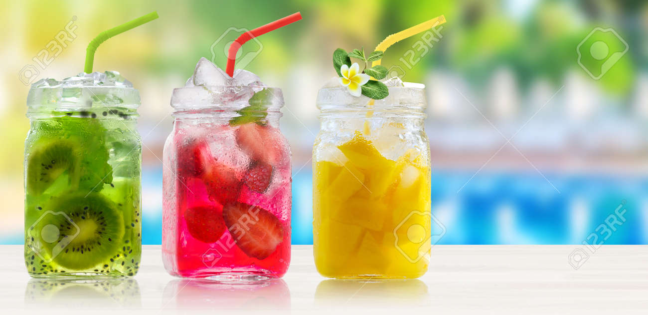 Summer refreshing exotic drinks cocktails in glass jars with straws on wooden counter on swiming pool background. - 170947485
