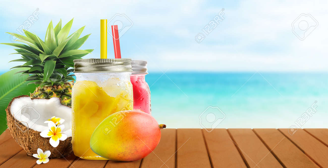 Summer tropical cocktail drinks of mango coconut juice and strawberry on blue turquoise sea background - 170744579