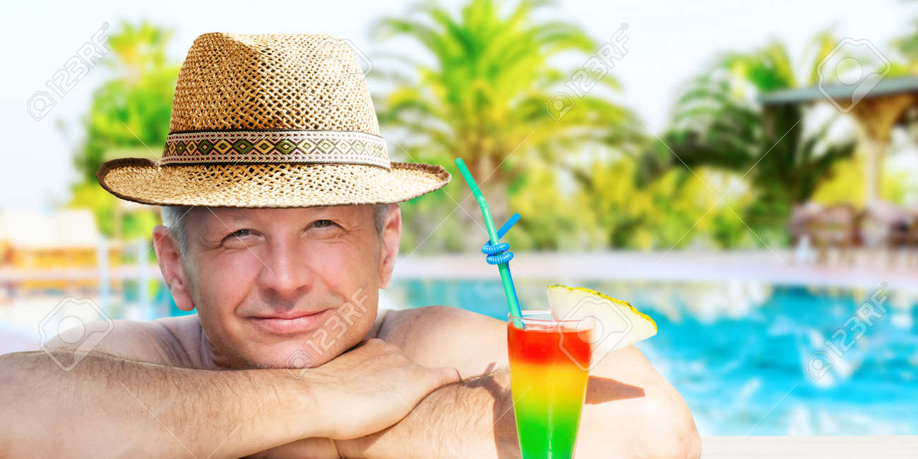 A man is enjoying his vacation relaxing with refreshing drink on the pool on resort hotel background. - 170947487