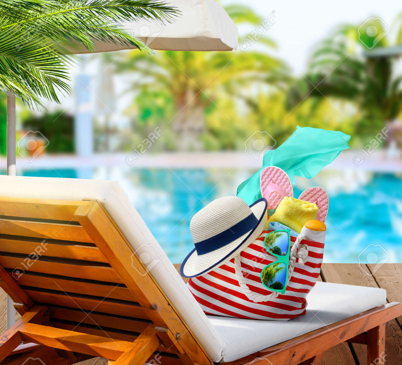 Beach bag with accessories on sun lounger near swimming pool in luxury resort - 171379344
