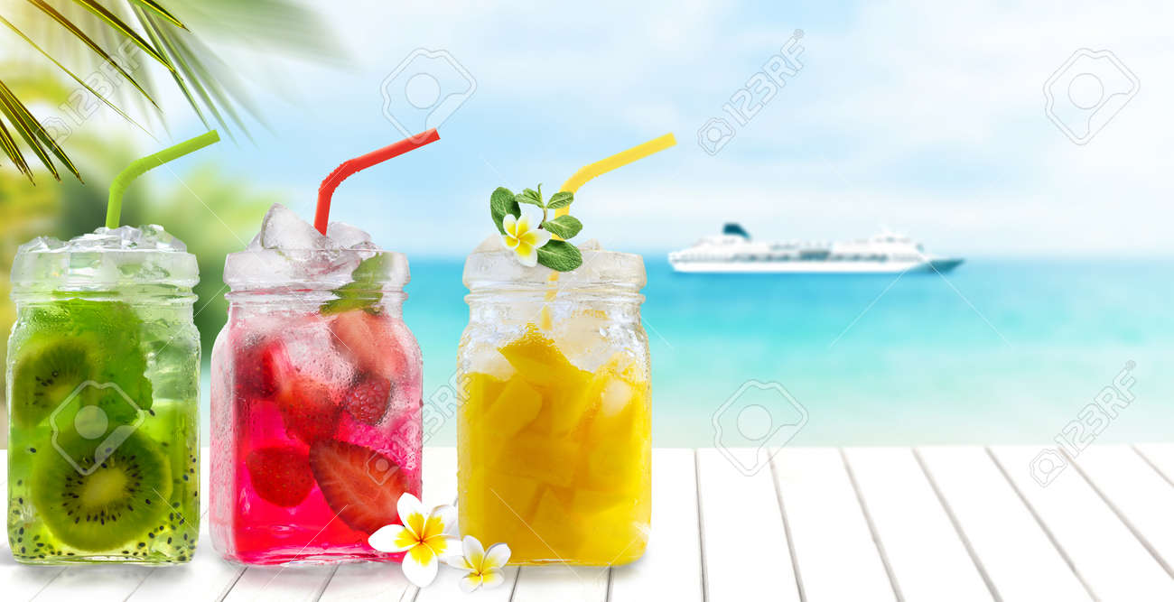 Summer cold exotic drinks cocktails in glass jars with straws on seascape with cruise ship background. - 171216242