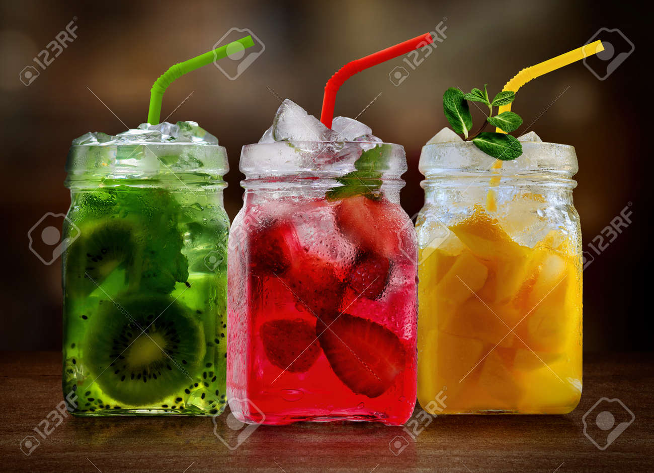 Refreshing fruits cocktails in glass jars on wooden table - 171548533