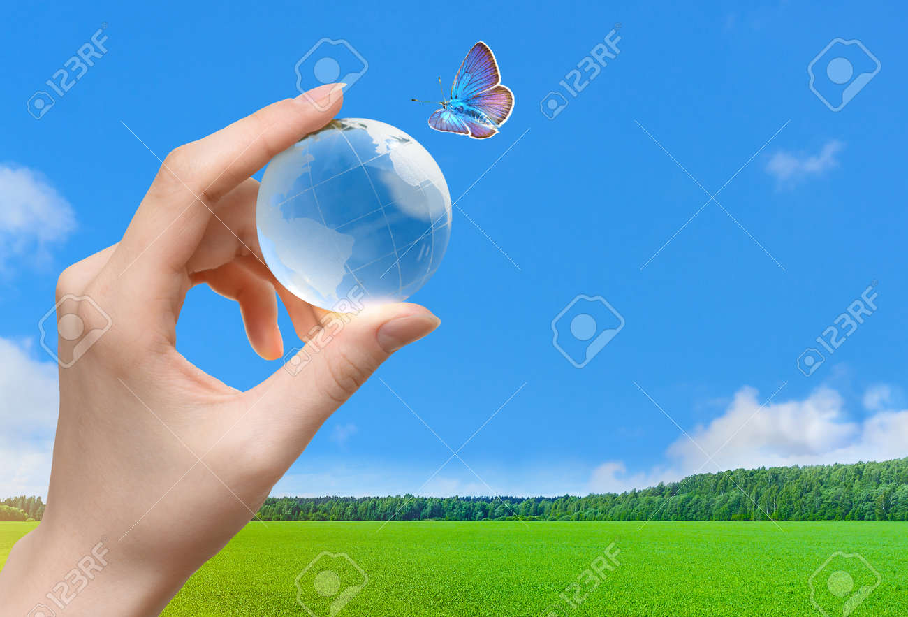 Glass globe of the planet Earth in human hand and flying butterfly - 171997688