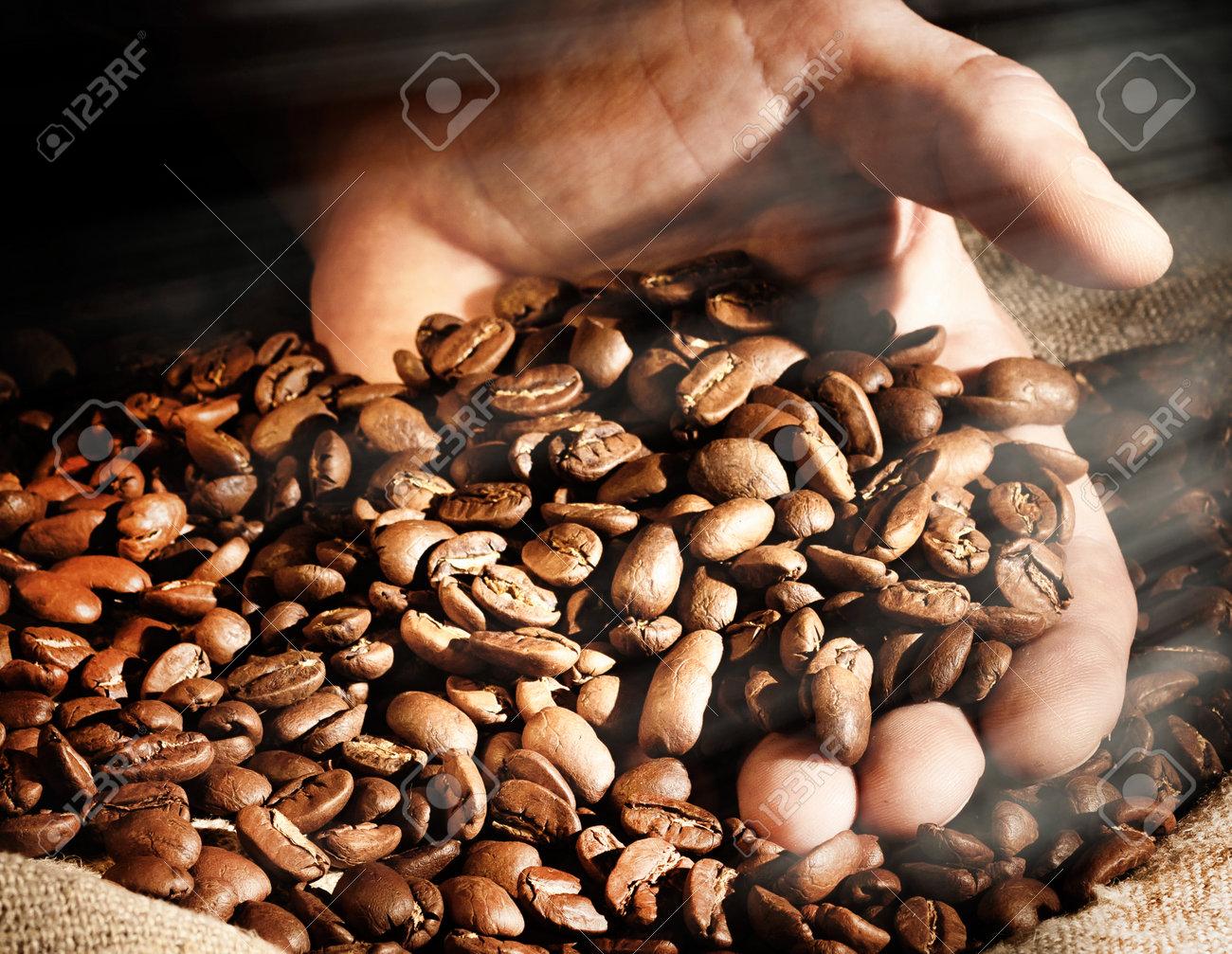Coffee beans in hand on dark background. - 171765777