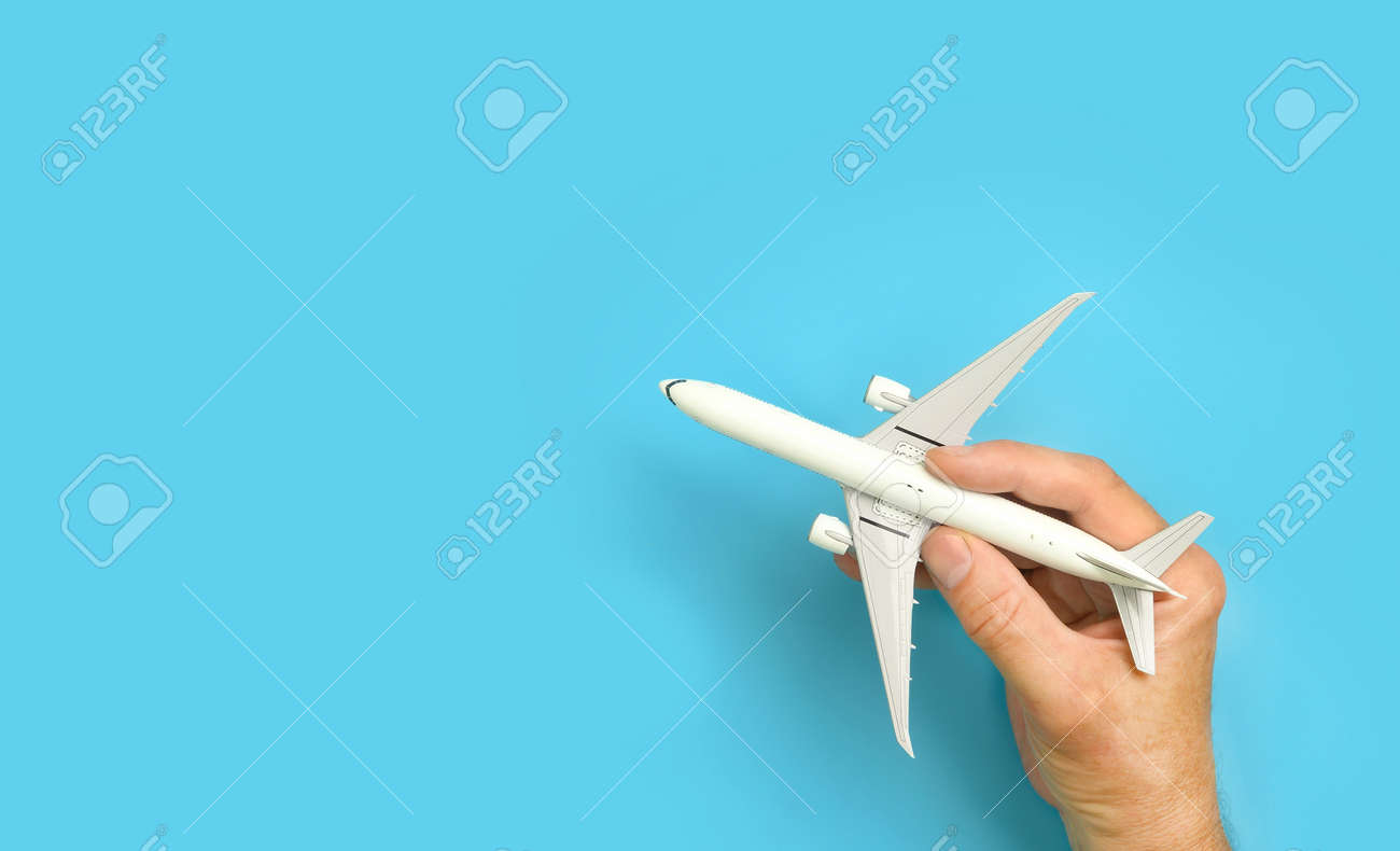 Male hand holding aircraft model, airplane in hand on blue background. - 172407706