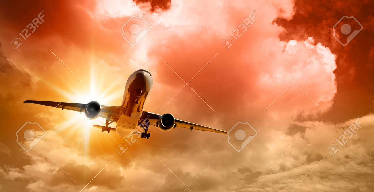 Airplane in the sky at sunset on dramatic crimson cloudy sky background - 172375121