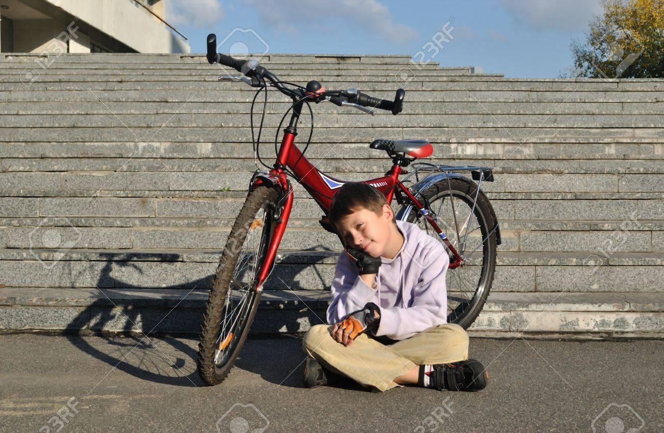 7863e628e El niño con la bicicleta roja Foto de archivo - 21976707