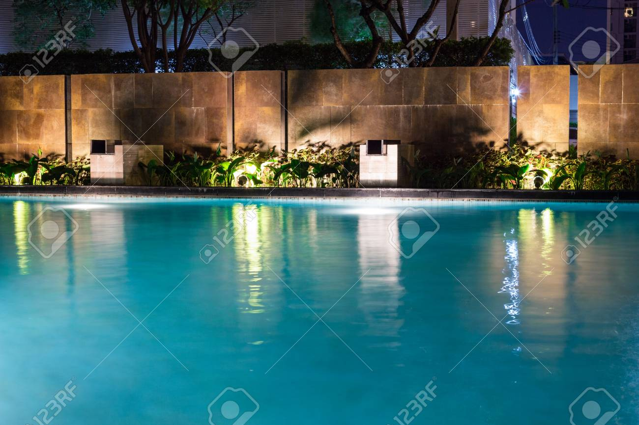 Lush pool lighting in backyard for luxury swimming pool design..