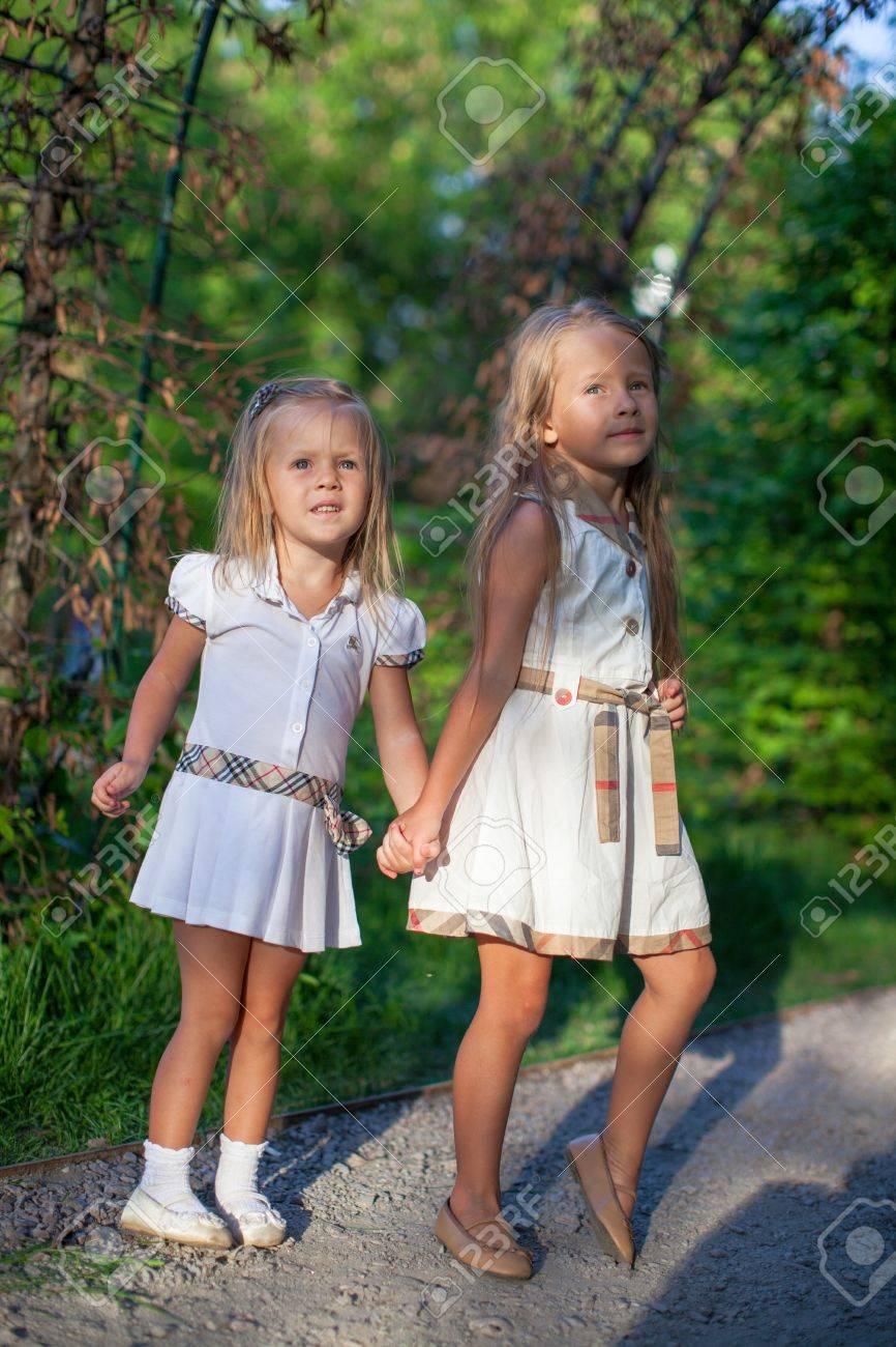 512ab977b955a Zwei Mode-süße Schwestern Gehen Hand In Hand Im Park Lizenzfreie ...