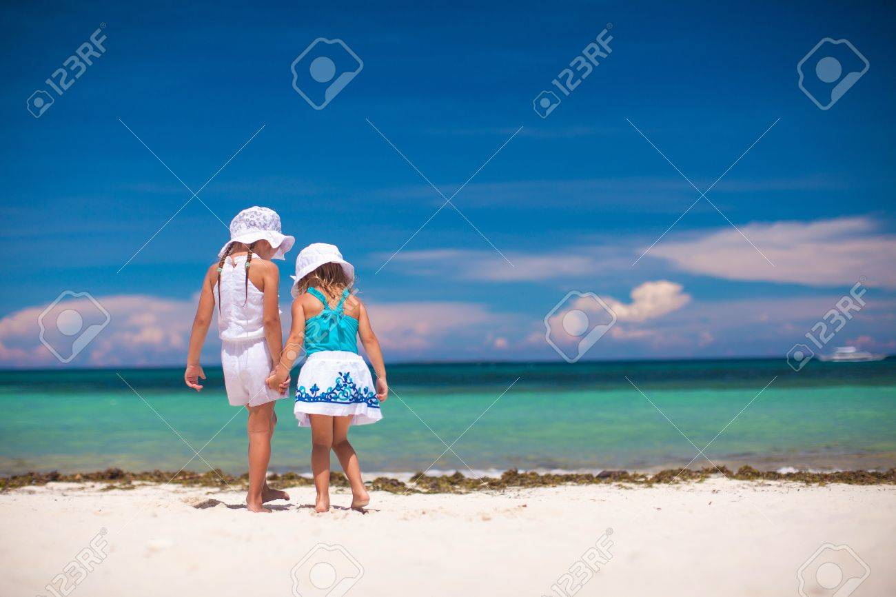 Back view of two little sisters looking at the sea on the white beach Stock Photo - 20756984
