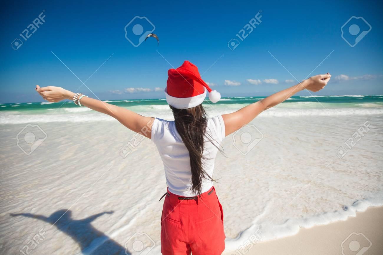 02e69a8c59c Back view of beautiful girl in santa hat walking like a bird on white beach  Stock