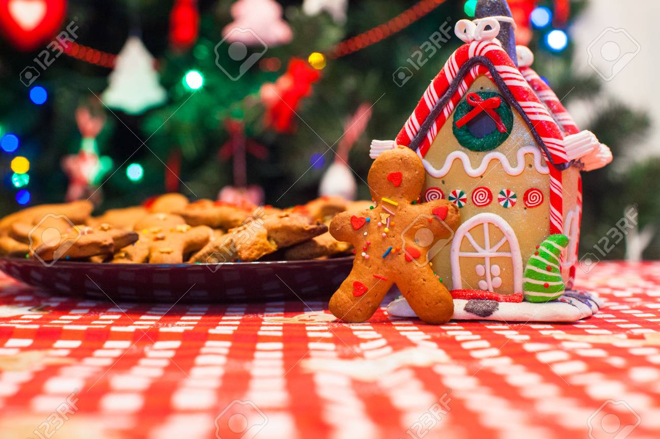 Christmas Gingerbread House Background.Cute Gingerbread Man In Front Of His Candy Ginger House Background
