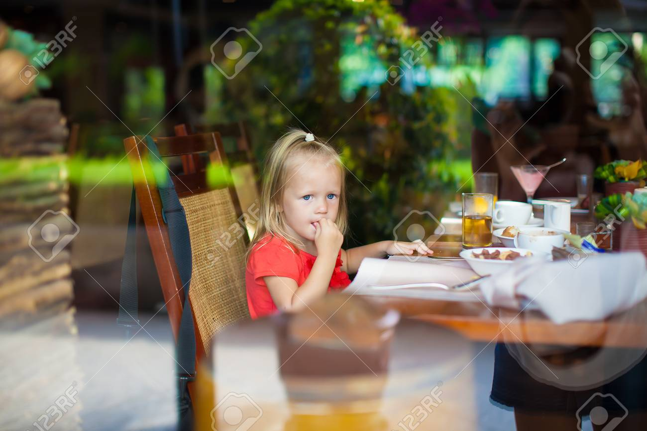 Adorable little girl in a beautiful cafe outside the window Stock Photo - 27019598