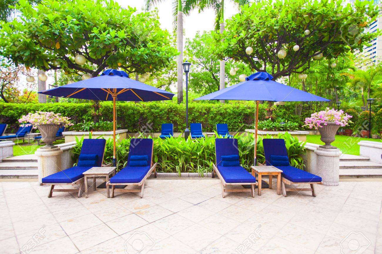 Beach beds with umbrellas near swimming pool in luxury hotel